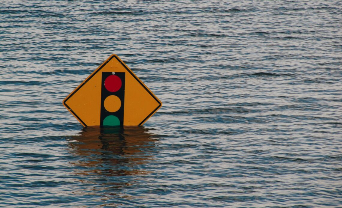 Traffic sign partially submerged in water during a flood