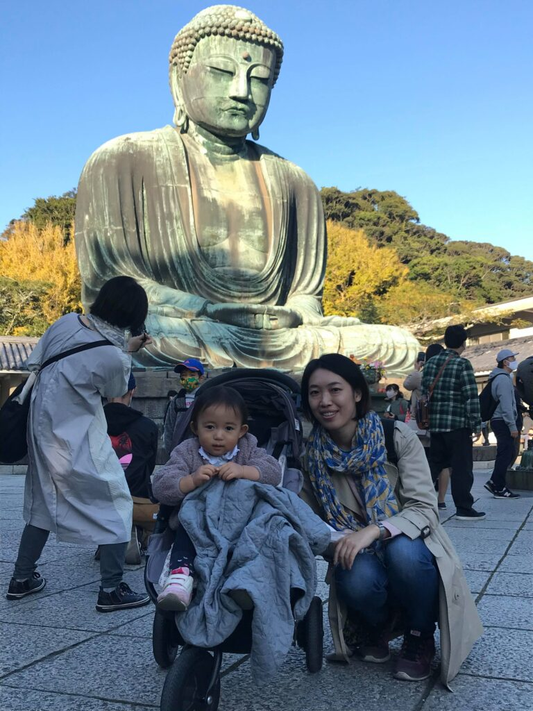 Miwa Naito crouches next to her niece, seated in a stroller, in front of a large statue outdoors at Kamakura.
