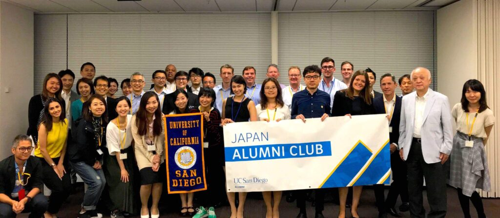 """Large group stands, with some members holding a white banner that reads Japan Alumni Club and another holding a navy banner with gold trim reading """"University of California San Diego"""" featuring the university seal in the center."""