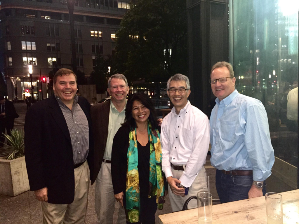 David Moore, Steven Howard, Marifel Verlohr, Yoshito Sakakibara and Gary Bremermann stand in front of a table.