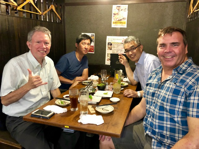 Four people are seated at a table, smiling for the camera and enjoying food and beverages.