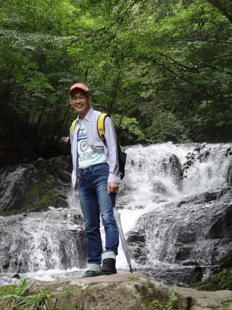 Yoshi Sakakibara stands in a lush, green area, with a cascading waterfall behind him.