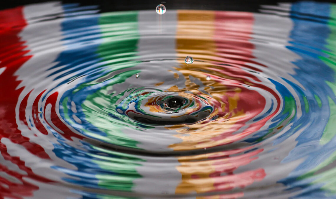 Water droplets creating ripples in a body of water with reflecting multicolors on its surface
