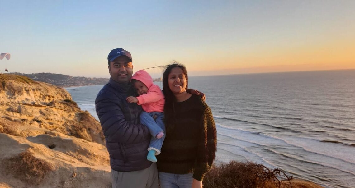 Deepika, her partner and her child stand on cliffs overlooking the ocean in San Diego.