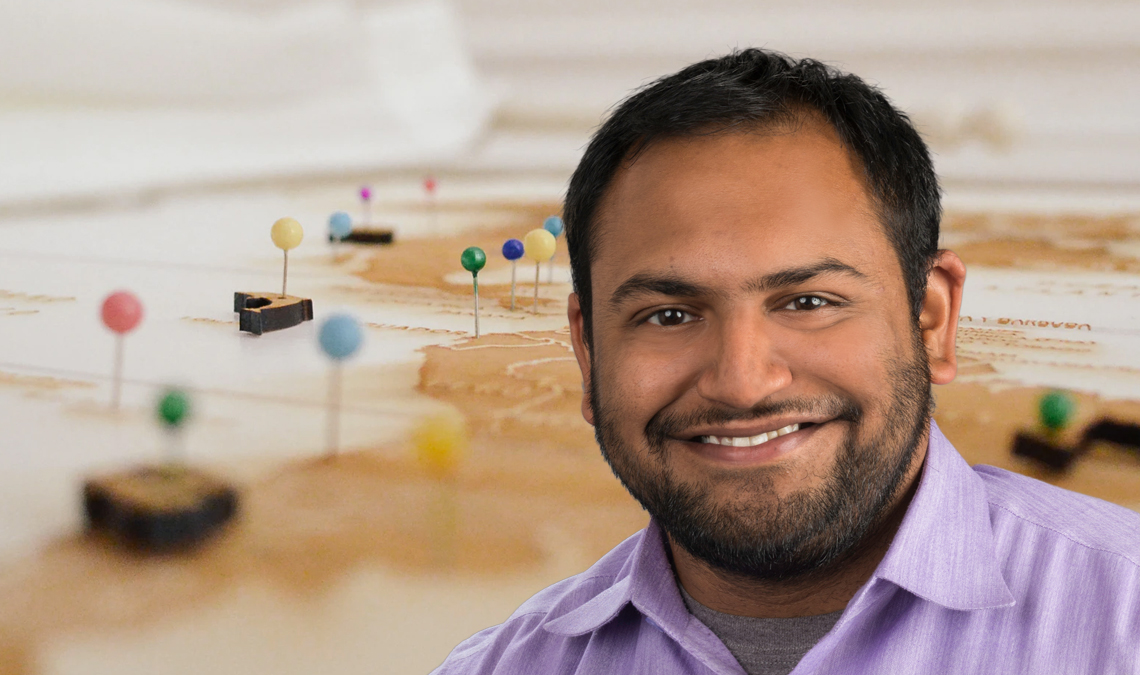Teevrat Garg's professional headshot in front of a map with pins.