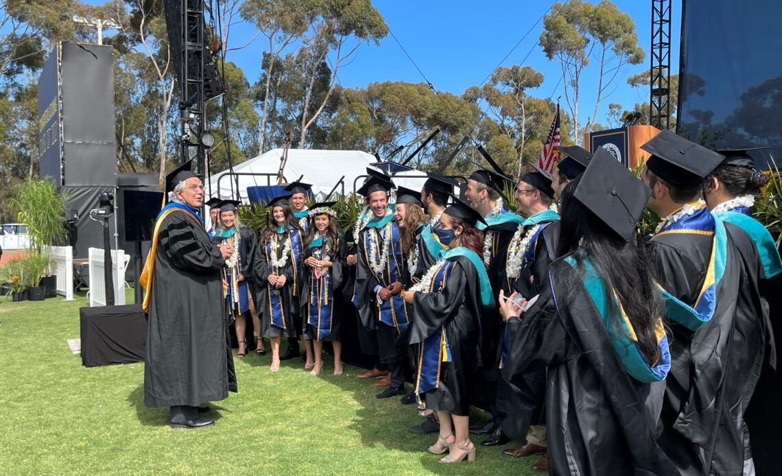 Dean Cowhey chats with graduates after the 2021 commencement ceremony.