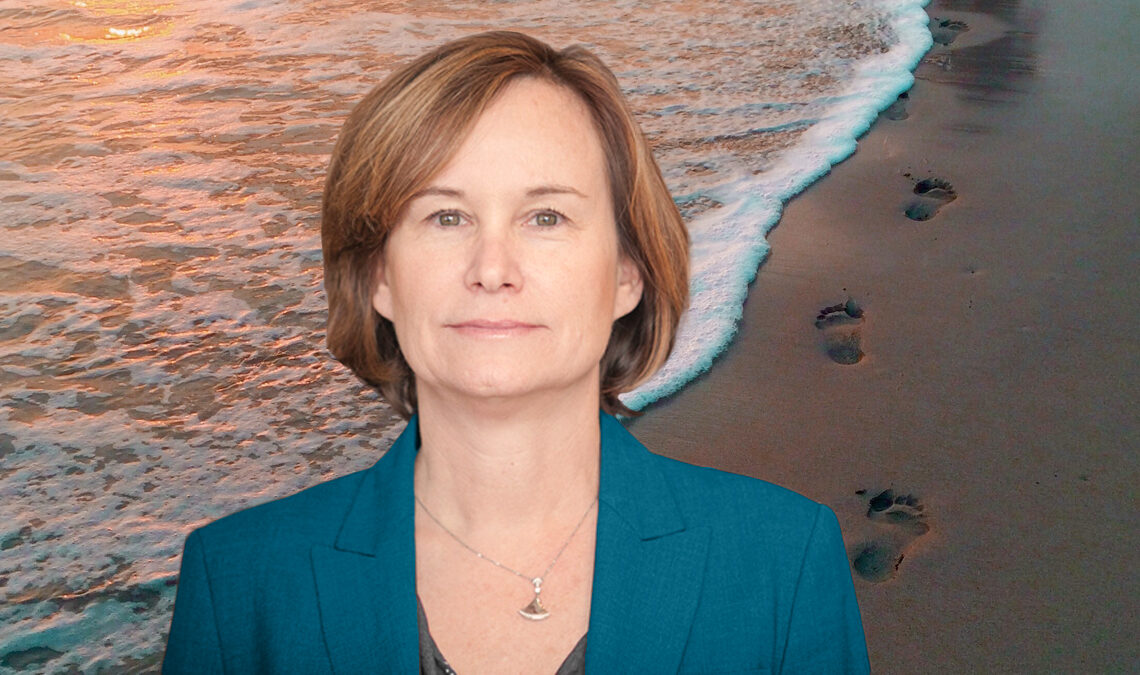 Caroline Freund against a backdrop of the beach shore, with footprints in the sand